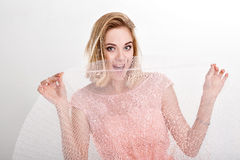 Beautiful blond woman in a pink cocktail dress dancing and havin Royalty Free Stock Image