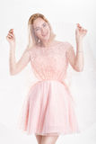 Beautiful blond woman in a pink cocktail dress dancing and havin Stock Photo