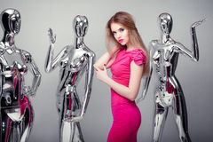 Beautiful blond woman in pink evening dress on background of man Stock Image