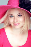 Beautiful blond woman in pink hat with makeup, smiling girl posi Stock Photography