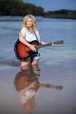 Beautiful Blond Woman Playing Acoustic Guitar in Water Stock Photos