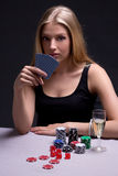 Beautiful blond woman playing poker in dark room Stock Image