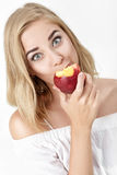 Beautiful blond woman with pleasure eating nectarine Royalty Free Stock Photos