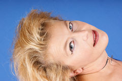 Beautiful blond woman portrait. Close-up of a beautiful blond woman looking at camera over light blue background Royalty Free Stock Photo