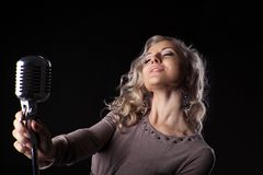 Beautiful blond woman portrait sing in microphone Royalty Free Stock Images