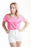 Beautiful blond woman. Poses in pink blouse and white short pants Stock Photo