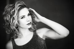 A beautiful blond woman posing like a model with her hand by her face in black and white. Royalty Free Stock Images