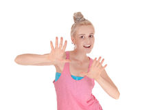 Beautiful blond woman pushing back. A lovely young blond Caucasian woman in a pink t-shirt holding her hands Stock Images