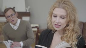 Beautiful blond woman reading the book aloud in the foreground while modestly dressed man studying material on the. Beautiful blond woman reading book in the stock video