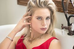 A beautiful blond woman in a red dress in a vintage tub. A beautiful blond woman with piercing blue eyes and jewelry with a long red dress on sitting in a Stock Photo