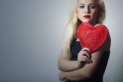 Beautiful Blond Woman with Red Heart. Beauty Girl. Show Love Symbol. Valentine's Day. Black Dress. Portrait of Beautiful Blond Woman with Red Heart. Beauty Girl royalty free stock photography