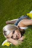 Beautiful blond woman relaxing on green grass Royalty Free Stock Photos