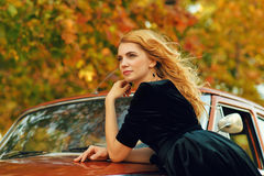Beautiful blond woman with a retro car in autumn Stock Images