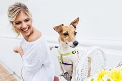 Beautiful, blond woman riding a bicycle in a town with her dog. Smiling Royalty Free Stock Images
