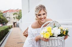 Beautiful, blond woman riding a bicycle in a town. Smiling Stock Photos