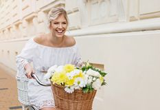 Beautiful, blond woman riding a bicycle in a town. Smiling Stock Image