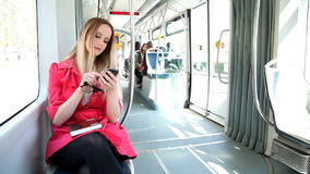 Beautiful blond woman riding tram, typing on mobile, phone, cell, holding glasses stock video