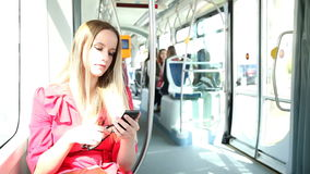 Beautiful blond woman riding tram, typing on mobile, phone, cell, holding glasses stock video footage