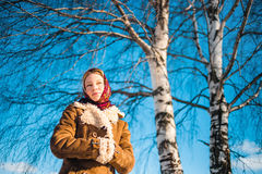 Beautiful blond woman in russian winter suit stay near the birch and thoughtfully looks afar. Girl clothed scarf Stock Photos