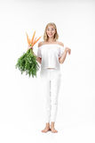 Beautiful blond woman showing rabbit and holding fresh carrot with green leaves on white background. Health and Diet Royalty Free Stock Image