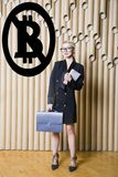 Beautiful blond woman showing standing near bitcoin sketch. Virtual money or btc crush concept. Cryptocurrency. stock photo