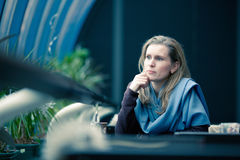 Beautiful blond woman sits in cafe Royalty Free Stock Images