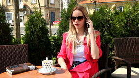 Beautiful blond woman sitting in coffee shop, talking on the phone stock video footage