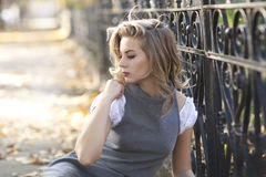 A beautiful blond woman sitting in front of a vintage black rod iron railing. A beautiful young blond woman sitting in a grey dress with white blouse sitting in Stock Image