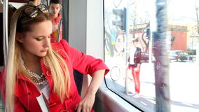 Beautiful blond woman sitting in tram, reading the book, answering phone stock video footage