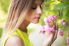 Beautiful blond woman smelling pink rose flowers. Sunny summer. Royalty Free Stock Photography
