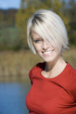 Beautiful blond woman smiling by a lake Royalty Free Stock Photography