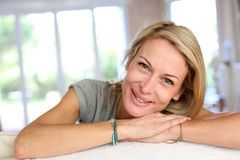 Beautiful blond woman smiling. Beautiful blond mature woman relaxing in sofa Royalty Free Stock Image