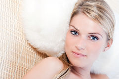 Beautiful blond woman at a spa. Relaxing on a grass mat with her head on a comfortable fluffy pillow Stock Image