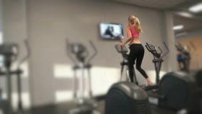 Athlete blonde engaged in the gym. Beautiful blond woman in sportswear is exercising on ski running sports simulator holding handles in the gym stock video footage