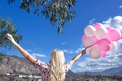 Beautiful blond woman standing and looking at a beautiful landscape and mountains. And he holds pink balloons in his hand. royalty free stock photo