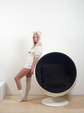 Beautiful blond woman standing next to round chair Stock Image