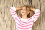 Beautiful blond woman standing outdoors laughing with hands in hair Stock Photos