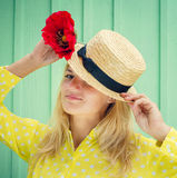Beautiful blond woman in straw hat holding a red flower Royalty Free Stock Image