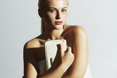 Beautiful blond woman.Stylish girl with white clutch.White bride dress Stock Photo