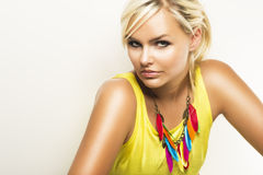 Beautiful blond woman with a sultry look. Beautiful blond woman giving the camera a sultry seductive look wearing a colourful trendy necklace, head and shoulders Royalty Free Stock Photography