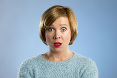 Beautiful blond woman in surprise and shock face expression expressing anxiety and fear Stock Photography