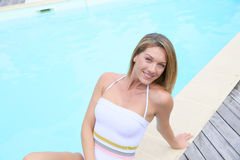 Beautiful blond woman by the swimming pool Royalty Free Stock Photo