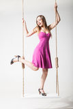 Beautiful blond woman on swing against white Royalty Free Stock Images