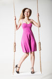 Beautiful blond woman on swing against white Stock Photo