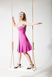 Beautiful blond woman on swing against white Royalty Free Stock Photography