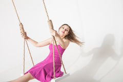 Beautiful blond woman on swing against white Stock Image