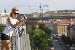Beautiful  blond woman taking pictures on her smartphone from the observation deck at Warsaw. Royalty Free Stock Photos