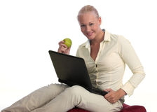 Beautiful blond woman telecommuting with laptop. Beautiful and young blond caucasian woman working from home on a laptop, sitting comfortably on a pillow, eating royalty free stock photo