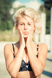 Beautiful blond woman touching cheeks lips in kiss stock images