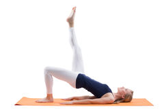 Beautiful blond woman training buttocks and hips muscles with straight one leg on a mat Royalty Free Stock Photos